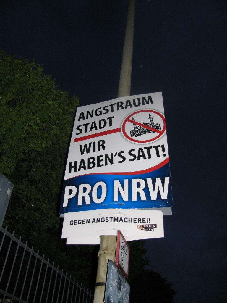 """Piraten-Störer """"Gegen Angstmacherei!"""" unter Pro NRW-Wahlplakat """"Angstraum Stadt, wir haben's satt!"""""""
