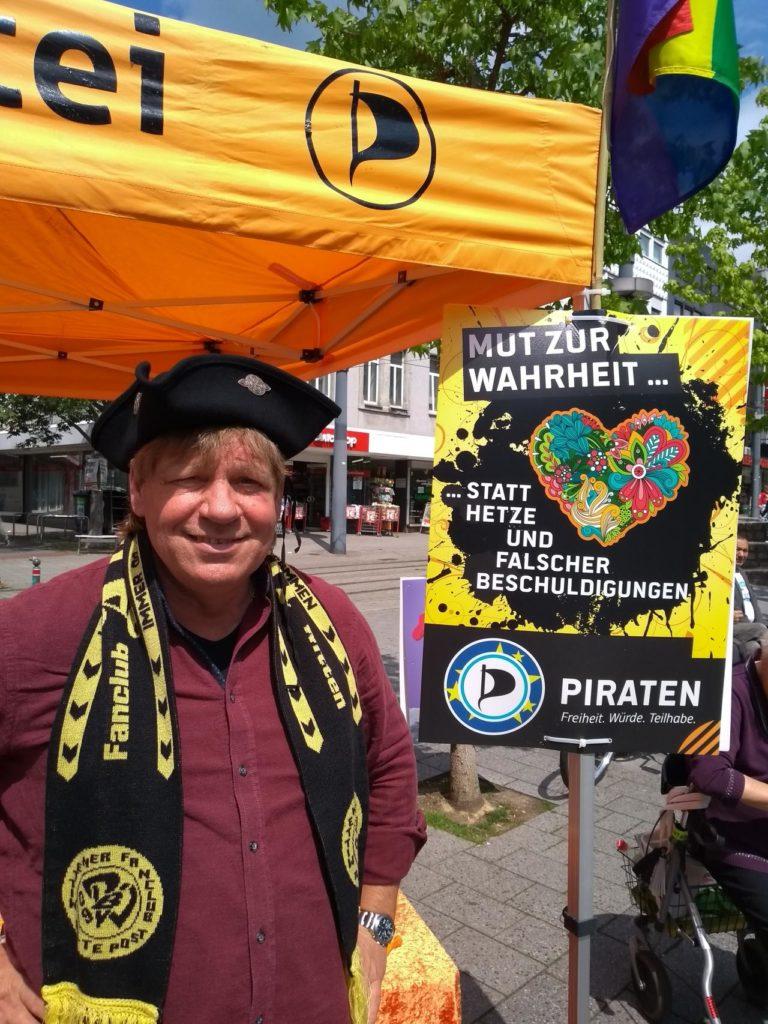 """Roland Löpke vor dem Plakat """"Mut zur Wahrheit"""""""