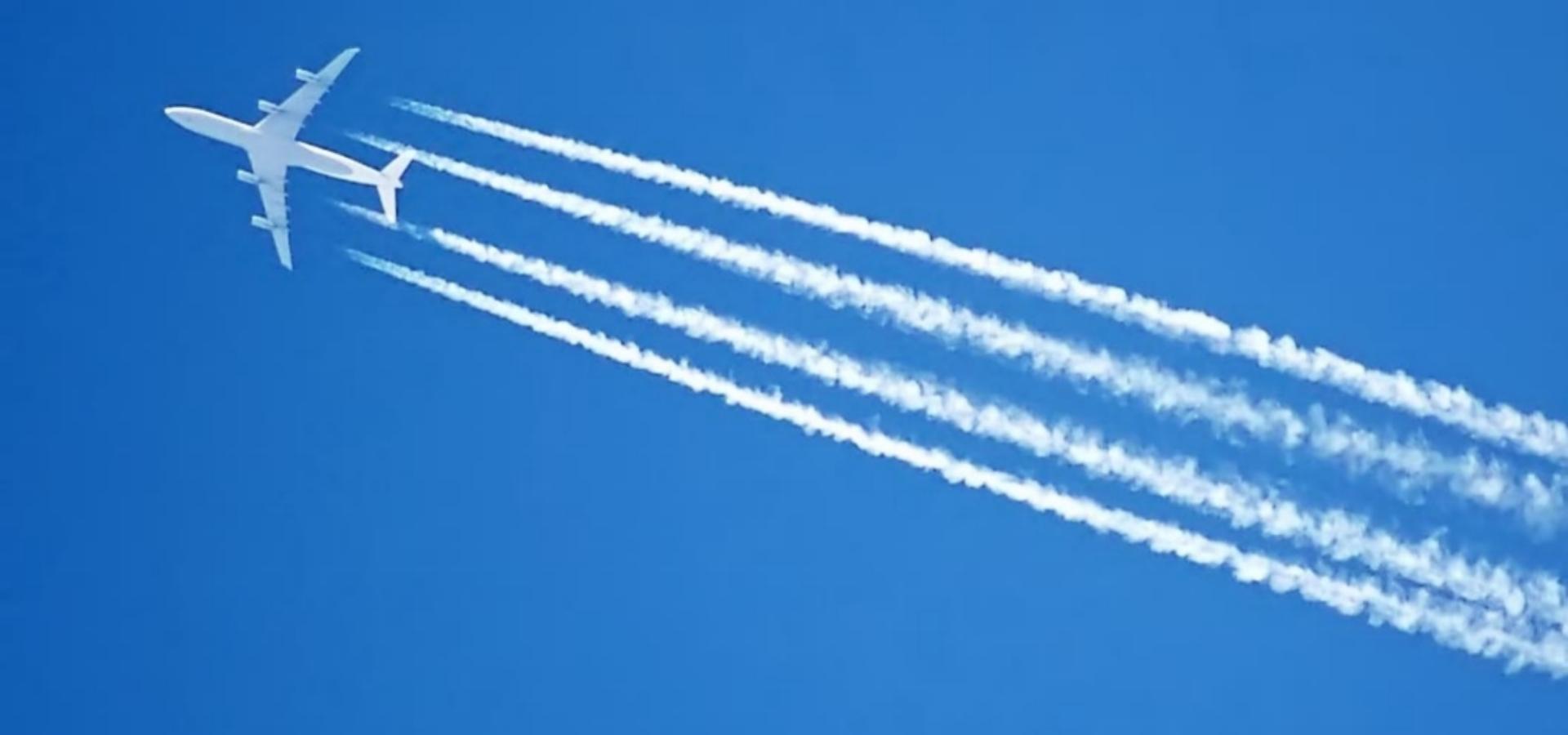 Flugzeug mit Kondensstreifen am Himmel