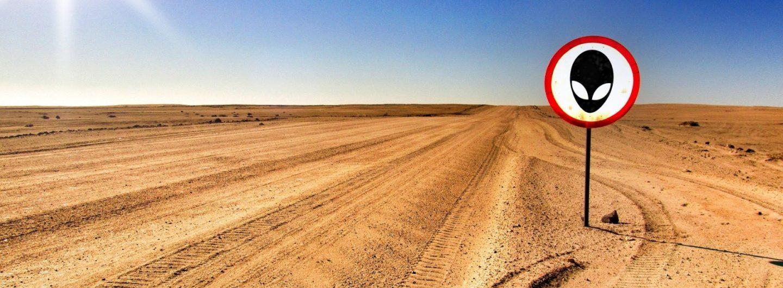 """Bild einer Wüste mit einem Verkehrsschild """"Achtung Aliens"""""""