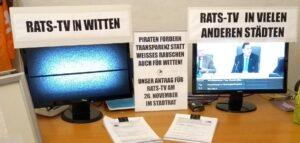 """Zwei Monitore. Auf dem Linken ist nur Weißes Rauschen zu sehen. Er ist überschrieben mit """"Rats-TV in Witten"""". Rechts auf dem Monitor sieht man eine Aufzeichnung einer Ratssitzung aus Wuppertal. Der rechte Monitor ist überschrieben mit """"Rats-TV in vielen anderen Städten"""". Zwischen beiden Monitoren steht ein Schild mit dem Text """"Piraten fordern Transparenz statt weißes Rauschen auch für Witten!"""""""
