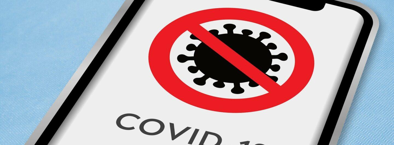Smartphone mit einem durchgestrichenen Corona-Virus auf dem Display.