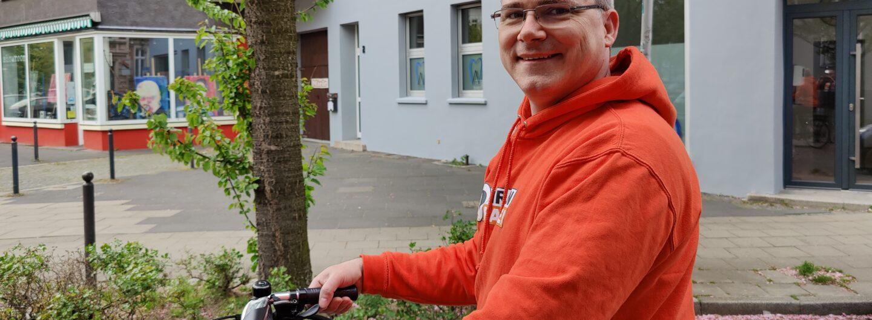 Eric Tiggemann auf einem Lastenrad und mit einem Piraten-Hoodie bekleidet. Im Hintergrund ein blühender Kirschbaum.